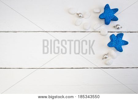 Background with white pearl necklace pendants beach pebbles and blue starfish on white wooden planks - concept of relaxation and luxury