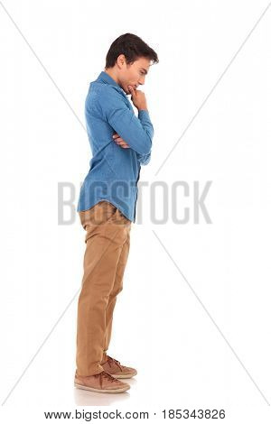 thoughtful young casual man looking down on white background
