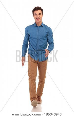 confident happy young casual man walking forward on white background