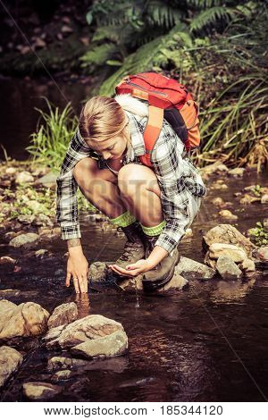Hiker woman drinking from stream