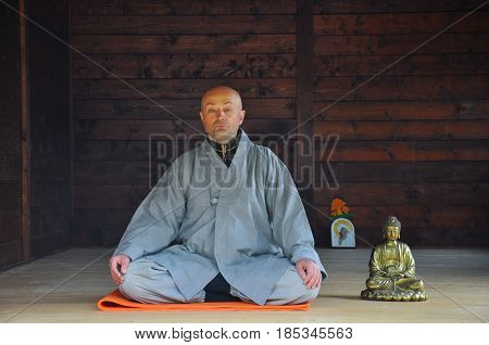 Buddhist Meditation. Older man meditating in a wooden house. Senior man practicing meditation with a Buddha Statue.