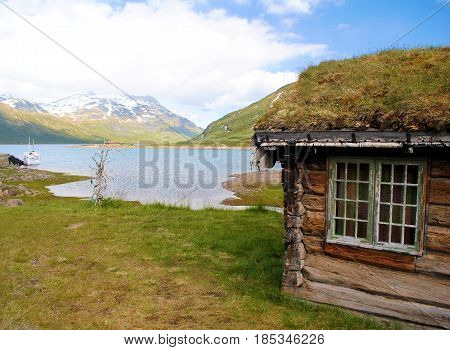 View on lake with deserted shed in Norway