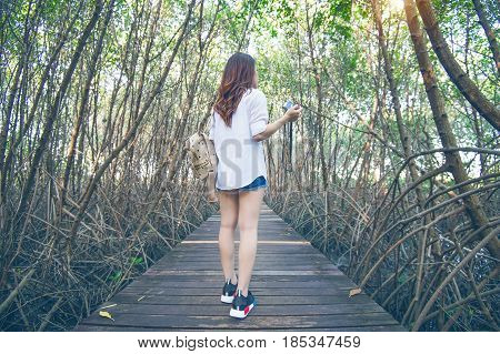 Girl walking alone and hand holding camera on a the wooden bridge.