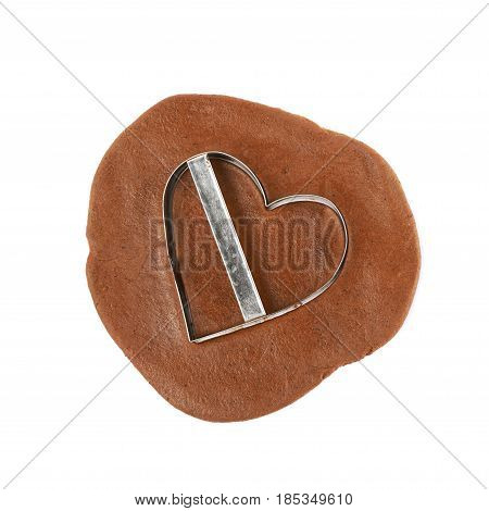 Rolled up thin layer of cookie dough and a heart shaped cookie cut out of it, composition isolated over the white background
