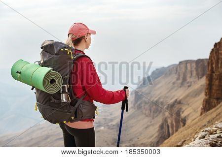 A slim, pretty girl hipster in a cap and a red jacket with sticks for Nordic walking with a backpack and a folded rug for relaxation stands in the mountains against the backdrop of rocks and distant Caucasian lands