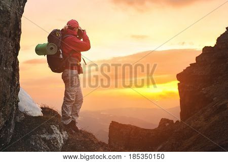 Girl photographer traveler with a backpack in the mountains photographing the sunset looking for adventure and creating masterpiece photos