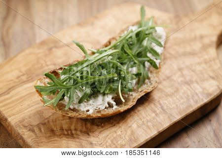 arugula on rustic bread with ricotta cheese, shallow focus