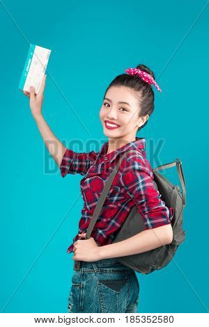 Woman Travel. Young Beautiful Asian Woman Traveler With Air Ticket On Blue Background