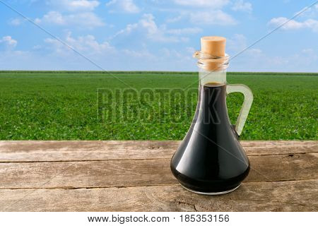 soy sauce in glass bottle on wooden table with green field on the background. Soybean field with blue sky. Photo with copy space area for a text. Seasoning soy sauce on a natural background