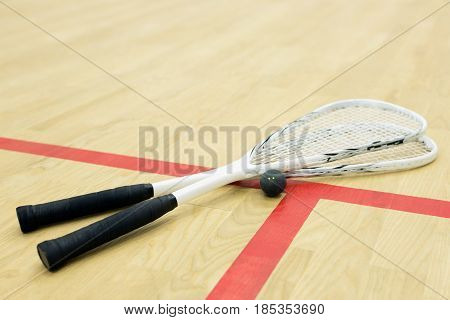 two squash rackets and ball on the wooden floor. Racquetball equipment on the court near red line. Photo with selective focus