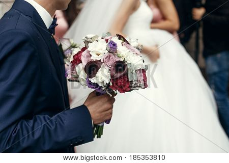 Stylish Groom And Bride With Rustic Bouquet, Posing In Morning Before Wedding Ceremony In Church