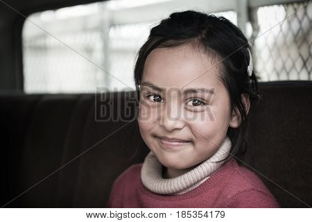 LEH,LADAKH,INDIA - MAY 7:Young unidentified Tibetan girl, smiling poses for a photo with her charming eye on May 7, 2014 in Leh Ladakh, Northern India. There are many Tibetan refugees living in Ladakh