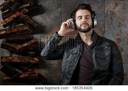 Caucasian man listening music on headphones, eyes closed.