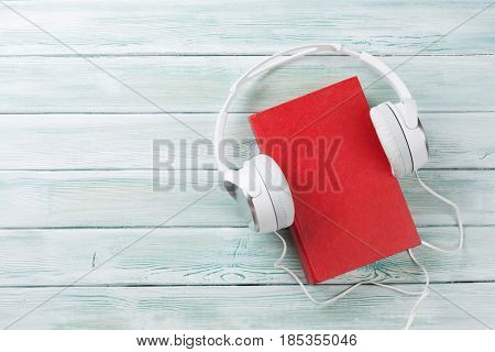 Audio book concept. Headphones and book over wooden table. Top view with space for your text