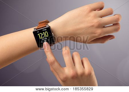 Naked female hand with smart wristwatch and digital clock on the screen