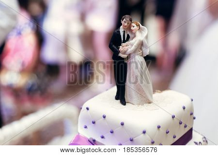 Bride And Groom On Wedding Cake. Figurines On Cake Top With Purple Icing, Luxury Wedding Reception,