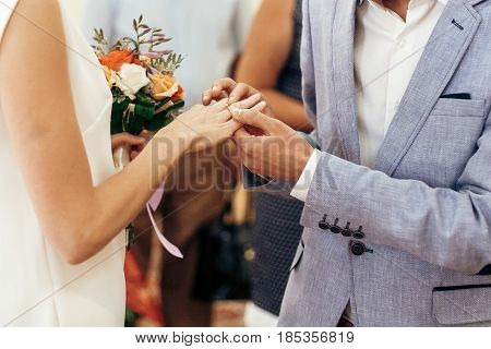 Bride With Bouquet And Groom Exchanging Wedding Rings At Wedding Registry. Stylish Couple Official W