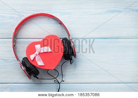 Music gift concept. Headphones and heart shaped gift box on wooden table. Top view with space for your greetings