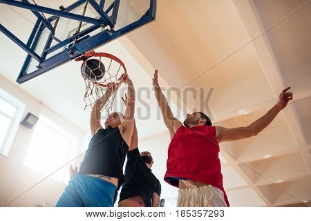 Low angle shot of basketball players playing basketball on the court.