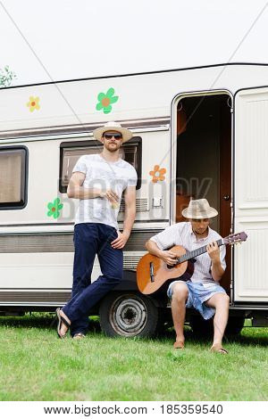 Two hipster friends chilling outdoors. Playing guitar, drinking. Holiday, spare time concept.
