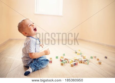 two years old child sitting on the floor. Pretty little boy palying with wooden cubes at home
