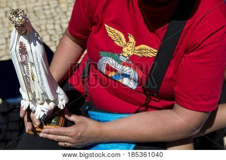 Fatima Portugal - May 13 2014: Woman holding a small statue of the Virgin Mary and wearing a Benfica shirt at the Sanctuary of Fatima during the celebrations of the apparition of the Virgin Mary in Fatima Portugal.