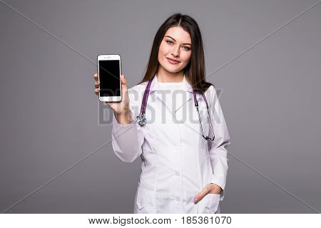 Young Doctor Woman Pointing On Cellphone Screen On Grey Background