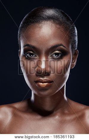Beauty Portrait Of African American Woman Looking Straight Into The Camera. Studio Portrait On Dark