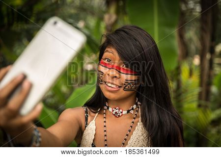 Native Brazilian girl from Tupi Guarani Tribe taking selfie photo, Brazil
