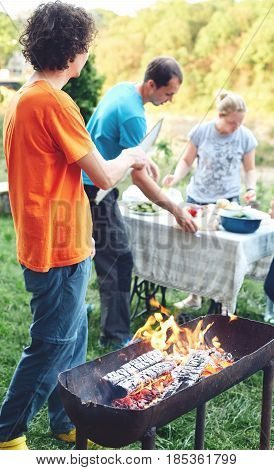flame grilled and wood burning in fire and people on BBQ party. family barbecue party in outdoor or home garden. A man blows coals in a fire with a sheet of cardboard.