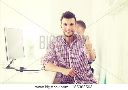 business, technology, education and people concept - happy young creative man or student with computer at office showing thumbs up