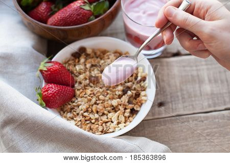 Healthy Breakfast. Muesli And Yogurt With Strawberries. A Woman's Hand Puts A Spoonful Of Yogurt In