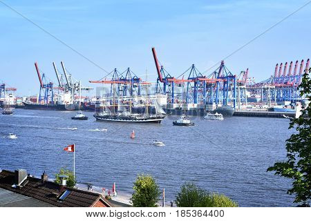 Hamburg harbor, birthday parade with various ships. View to Hamburg harbor with harbor cranes.