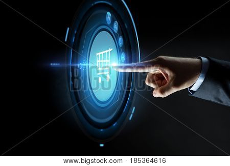business, people, e-commerce and technology concept - close up of businessman hand pointing finger to shopping cart icon over black background