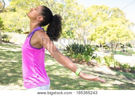 Female jogger stretching her arms in the park