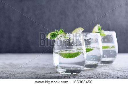 Sparkling water with piece of lime in glass on a dark background. detox water
