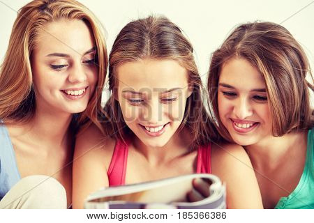 friendship, people and pajama party concept - happy friends or teenage girls reading magazine at home