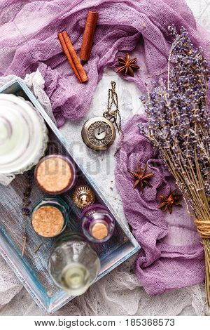 Lavender background with bouquet and twigs of dry lavender bottle with cosmetic oil perfume bottle vintage pocket watch cinnamon sticks anise stars and cosmetic salt. Spa and perfume theme. Top view.