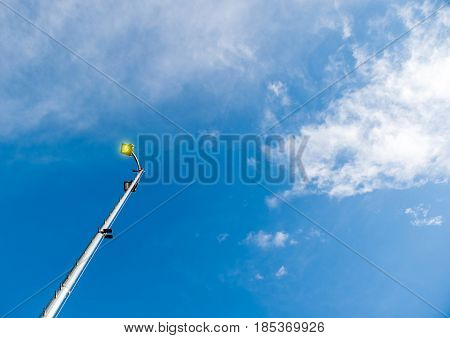 Lighting pole LED street lamp seen from below against blue spring sky with beautiful cloud - yellow pure light coming from the bulb