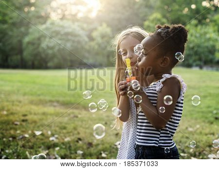 Group of Diverse Kids BLowing Bubbles Together at the Field