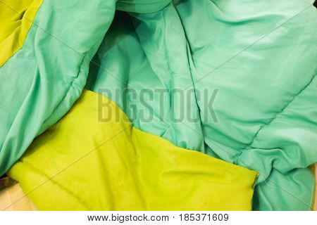 Green duvet and on an unmade bed