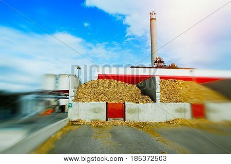 Blurred Bio Power Plant With Storage Of Wooden Fuel (biomass) Against Blue Sky