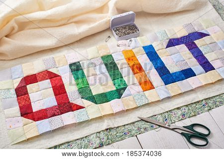 The word quilt sewn from colorful square and triangle pieces of fabric