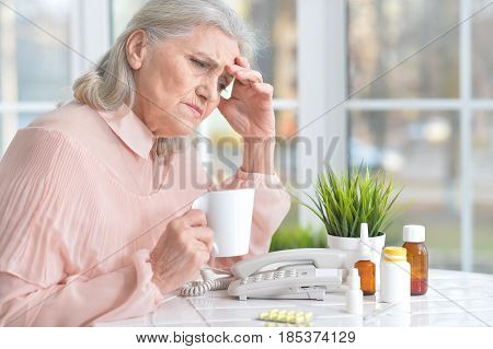 Portrait of a beautiful old woman taking pills