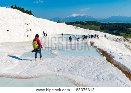 PAMUKKALE, TURKEY- APRIL,12: Tourists on Pamukkale travertines on April 12, 2015 in Pamukkale, Turkey. Pamukkale, UNESCO world heritage site, nowadays become one of the most visited sights in Turkey.