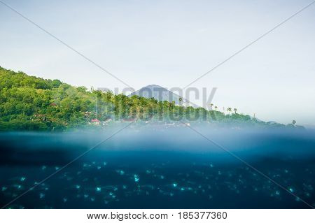 Underwater, fish, blue water in tropical ocean and volcano in Amed. Bali, Indonesia