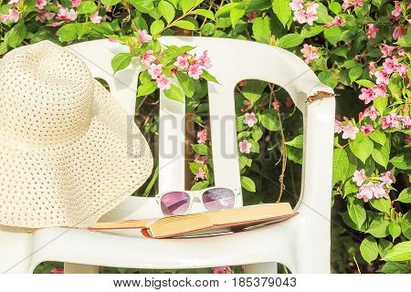 Garden chair a book a white hat and sunglasses near to a flowering weigela in a summer garden close-up