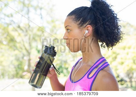 Close-up of female jogger drinking water in the park