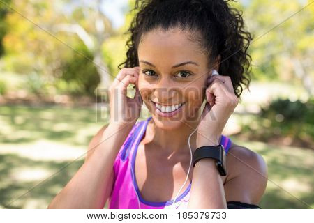 Close-up of smiling jogger woman adjusting her headphones in the park