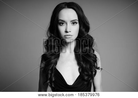 Black and white studio fashion photo of natural beautiful yong woman on gray background. Health and beauty